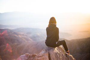 femme en haut d'une montagne après une randonnée
